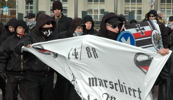 """Afschrikkende beelden van NVU demonstranten op 27 januari 2007 in Apeldoorn. Het spandoek is getooid met nep-AFA-logo's """"National Sozialistische Aktion"""" (zie hier)"""