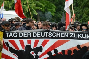 Paul Peters met capuchon achter het kopspandoek van de demonstratie 'Tag der Deutsche Zukunft' in Hamburg, juni 2012