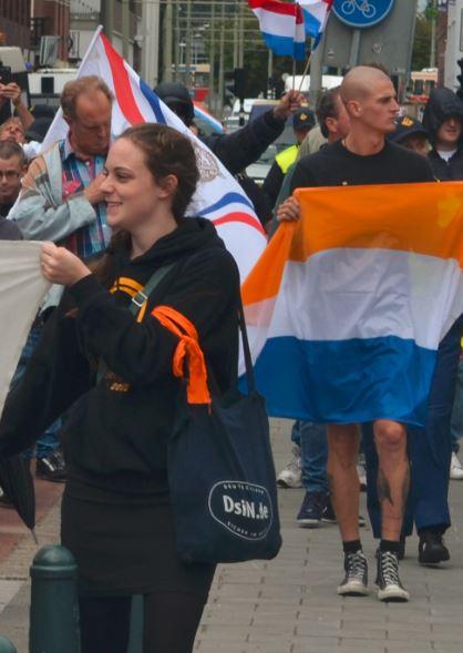 Gertrud Bossdorf van Identitair Verzet. Achter haar een man met prinsenvlag