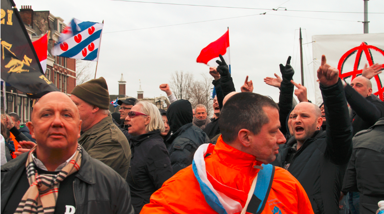 Adé Jansen (links, met DTG-shirt) op Pegida demonstratie Amsterdam, februari 2016. Rechts achter hem DTG-activisten